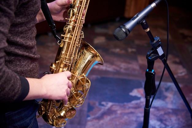 Saxofone dourado nas mãos de um músico perto do microfone.
