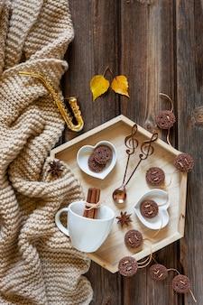Saxofone e folhas de outono dourados pequenos e uma bandeja com copo e cookie. outono