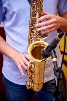 Saxofone nas mãos de um músico.