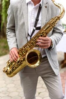 Saxofonista com saxofone se prepara para se apresentar no feriado