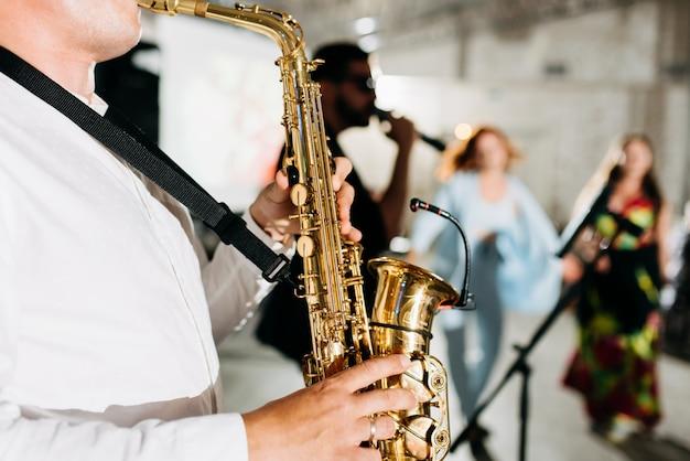 Saxofonista com vocalista e banda de jazz musical
