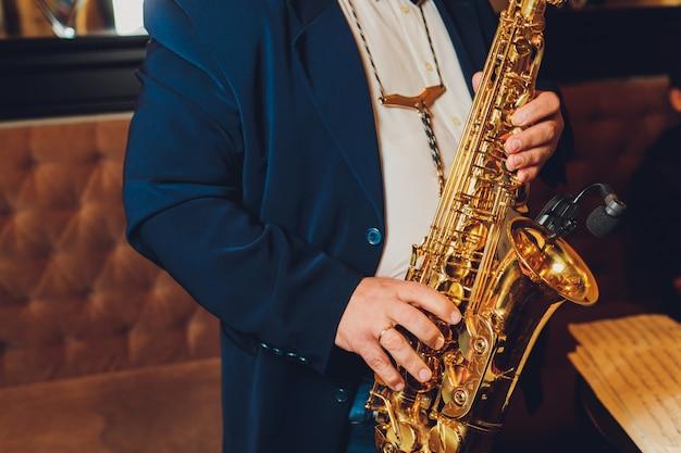 Saxofonista do instrumento de música clássica do saxofone com o close up do saxofone alto no preto.