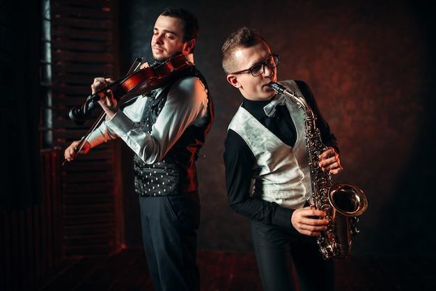 Saxofonista e violino tocando melodia clássica, dueto musical. jazz-man e violinista