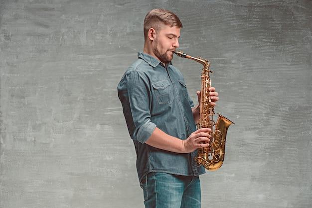 Saxofonista feliz tocando música no saxofone sobre cinza