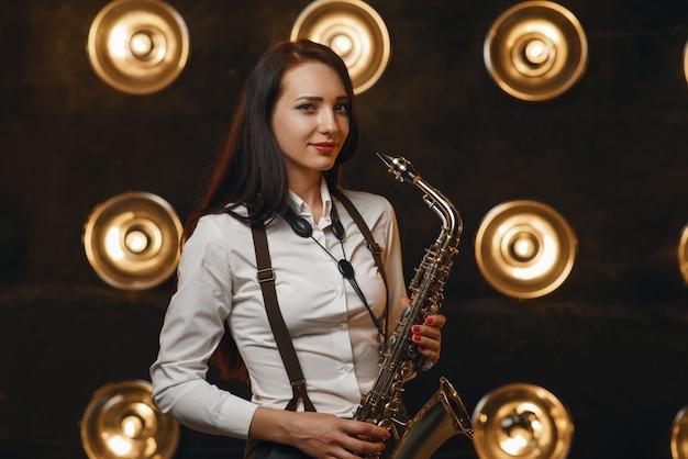 Saxofonista feminina tocando saxofone no palco