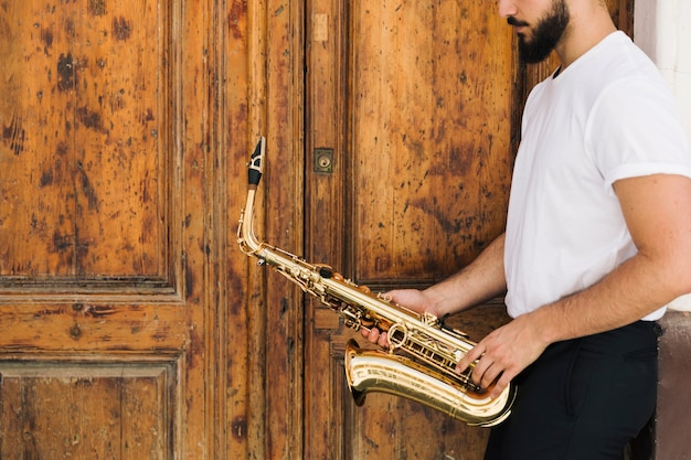 Saxofonista lateral com fundo de madeira