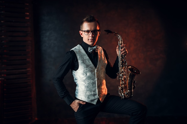 Saxofonista masculino posando com saxofone, homem do jazz.
