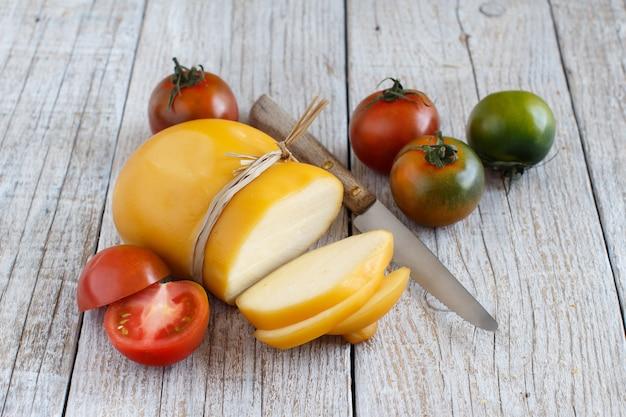 Scamorza com tomate e faca em uma mesa de madeira