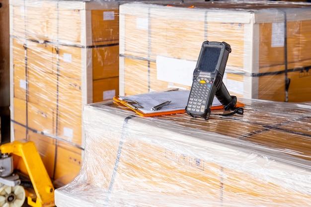 Scanner de código de barras e caixas de pacote em ferramentas de trabalho de computador do armazém de armazenamento para estoque de armazém