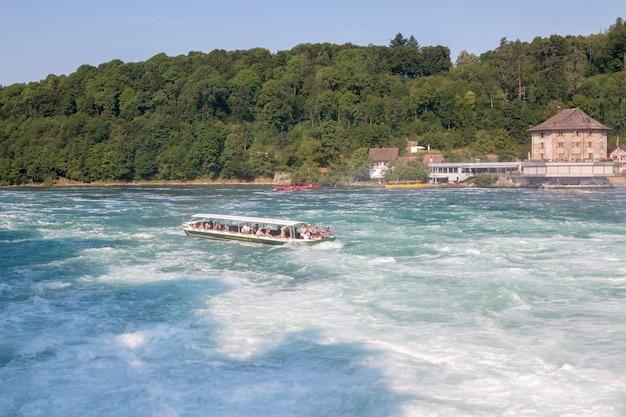 Schaffhausen, suíça - 22 de junho de 2017: barco com pessoas flutuando para a cachoeira das cataratas do reno. é uma das principais atrações turísticas. dia de verão com céu azul