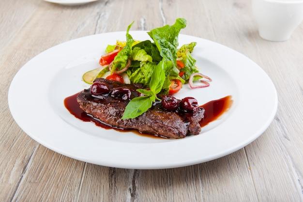 Schnitzel de carne com molho de cereja e vegetais