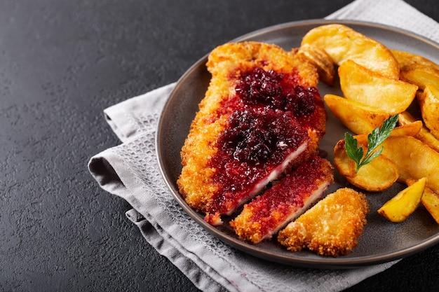 Schnitzel de frango com batata idaho em um prato escuro