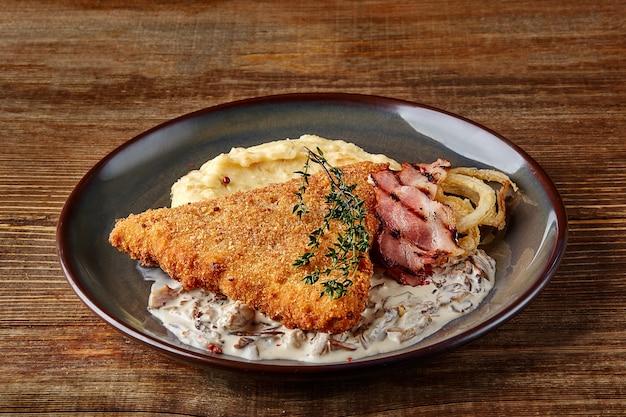 Schnitzel de frango com purê de batata de ervas e molho de cogumelos no prato no fundo da mesa de madeira.