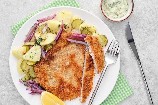 Schnitzel de viena com batatas e cebolas.