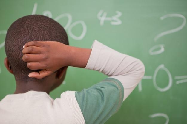 Schoolboy pensando com a mão na cabeça
