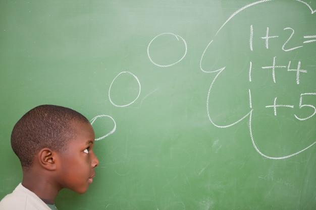 Schoolboy pensando em adições