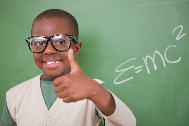 Schoolboy posando com a fórmula de equivalência de energia em massa e