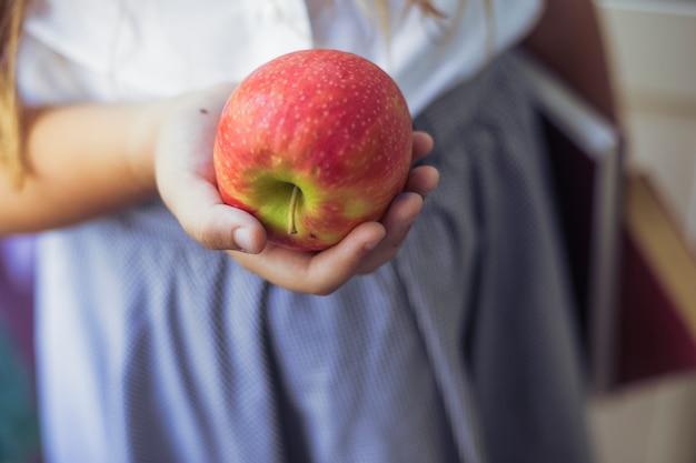 Schoolgirl, com, maçã, em, mão