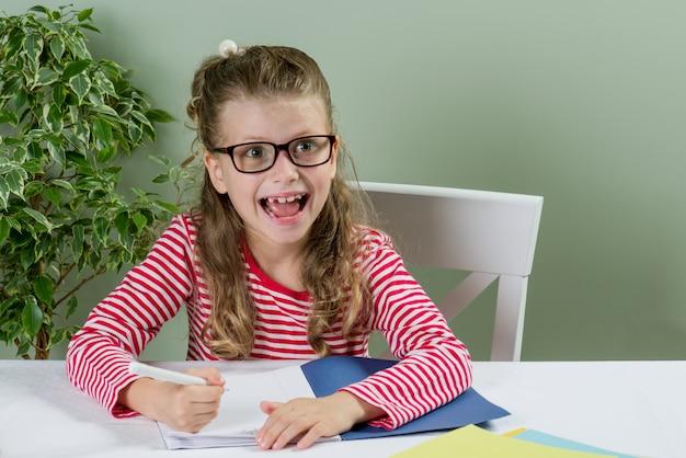 Schoolgirll em óculos escrevendo