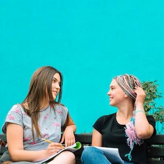 Schoolgirls posando no banco com estudos