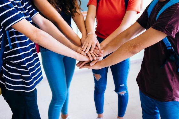 Schoolkids juntando as mãos