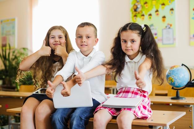 Schoolkids sentado na mesa dando polegares para cima