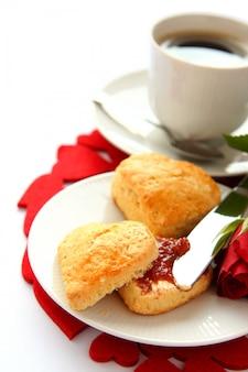 Scones em forma de coração com geléia de morango e uma xícara de chá