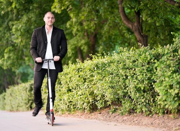 Scooter ativo da equitação do homem de negócios ao ar livre
