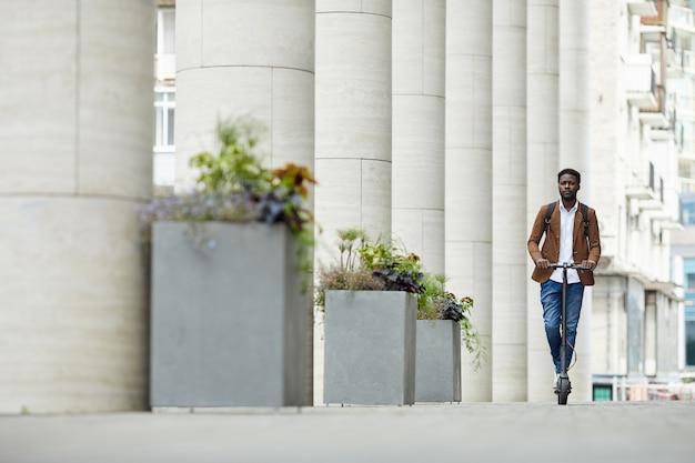 Scooter de equitação homem afro-americano na cidade