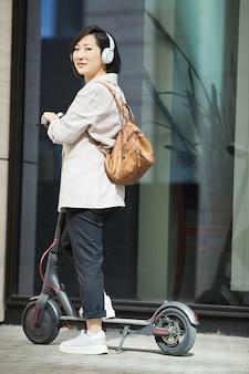 Scooter de equitação mulher asiática moderna na rua