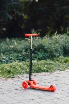 Scooter de impulso vermelho na passarela no parque