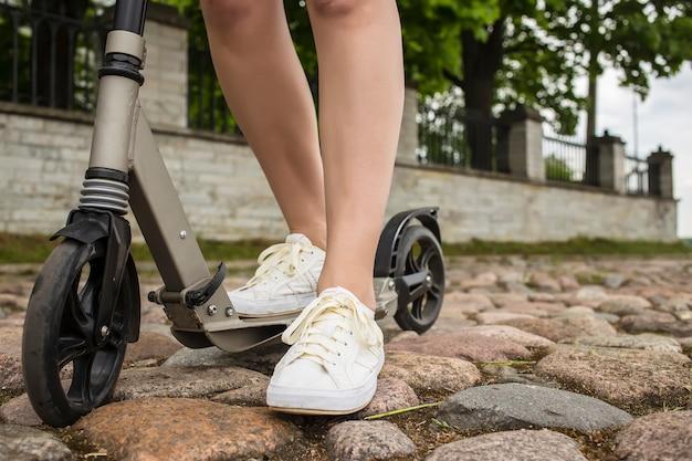 Scooter e pés de um homem que está na calçada de pedra na europa