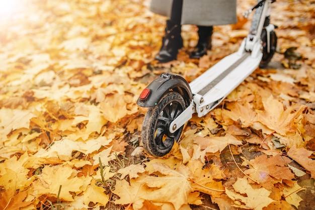 Scooter elétrica em um parque de outono andando em veículos elétricos no tempo frio