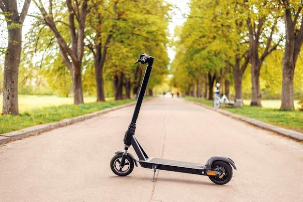Scooter elétrica no parque. navegando entre as laranjeiras verdes em uma estrada. ecotransporte moderno. preocupação com o meio ambiente.