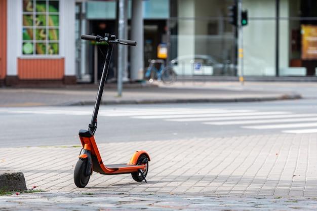 Scooter elétrica ou e-scooter estacionada na calçada, rua da cidade turva
