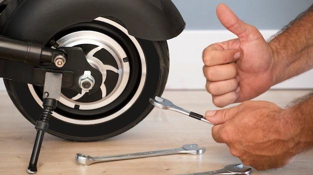 Scooter elétrico e mãos de mecânico fazendo gesto ok conceito de serviço de manutenção de scooter elétrico