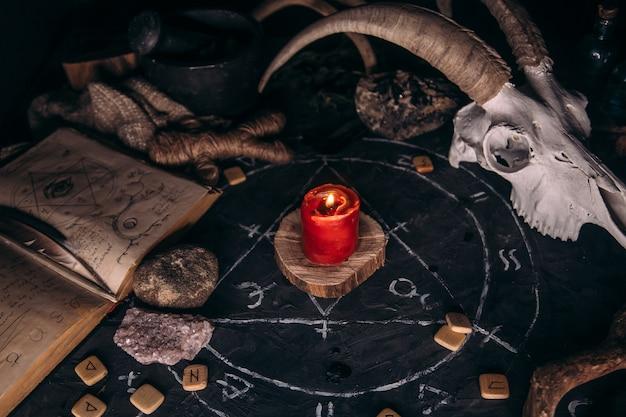 Scull de cabra branca com chifres, livro antigo aberto com feitiços, runas, velas e ervas na mesa de bruxa.