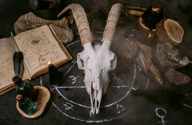 Scull de cabra branca com chifres, livro antigo aberto com feitiços, runas, velas pretas e ervas na mesa de bruxa.