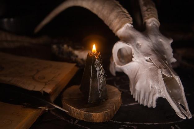 Scull de cabra branca com chifres, livro antigo aberto, velas pretas na mesa da bruxa. dia do conceito morto