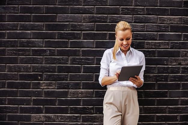 Sdmiling loira elegante empresária em frente a uma parede preta e usando o tablet.