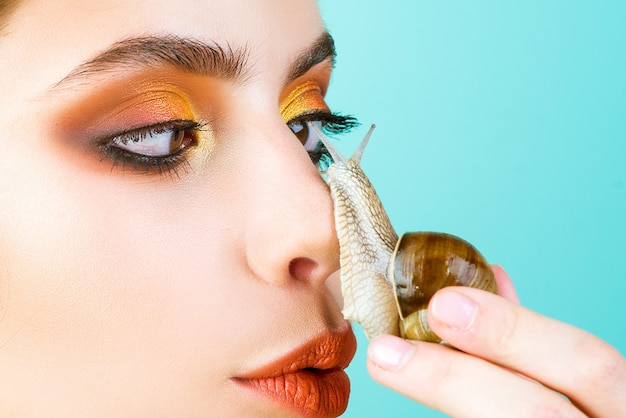 Se divertindo com o adorável caracol. cosméticos e muco de caracol. rosto de maquiagem na moda da menina e caracol bonito.