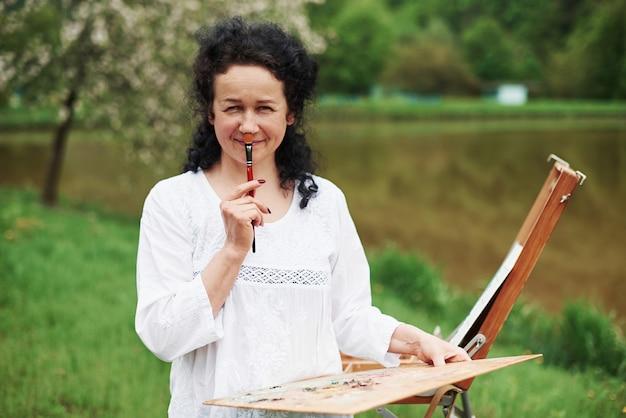 Se divertindo durante o processo. retrato de um pintor maduro com cabelo preto encaracolado no parque ao ar livre