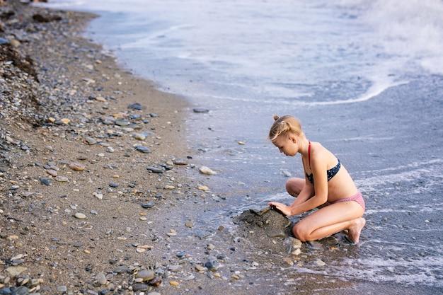 Se divertindo e alegria. loira linda menina com duas tranças brincando com areia do mar.