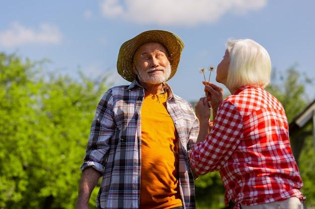 Se divertindo. esposa grisalha usando camisa quadrada soprando dente de leão no marido aproveitando o dia de verão