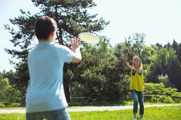 Se divertindo. feliz mãe magra jogando com seu filho enquanto relaxa ao ar livre