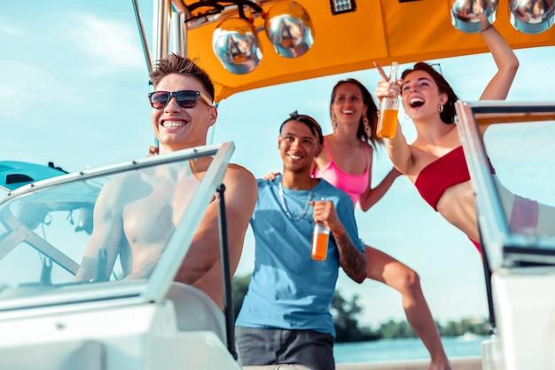 Se divertindo. jovem bonito dirigindo um barco a motor enquanto um grupo de amigos risonhos está atrás dele