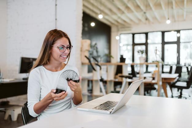 Se divertindo no trabalho. mulher de negócios nova que olha a tela do portátil ao jogar com um brinquedo.