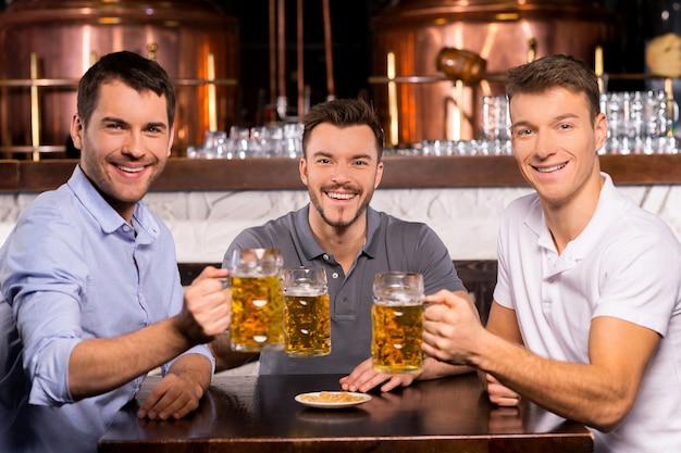 Se divertindo. três amigos alegres segurando canecas com cerveja e sorrindo para a câmera