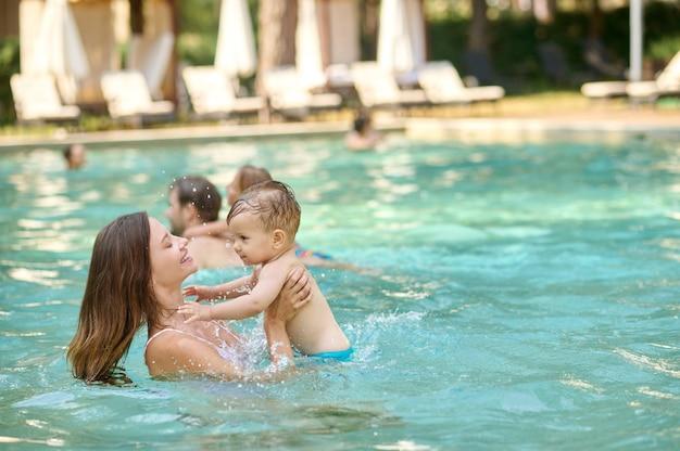 Se divertindo. uma jovem família se divertindo em uma piscina e parecendo curtida