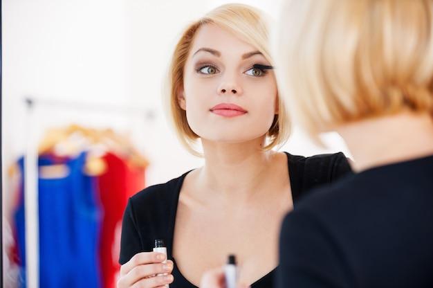 Se preparando para a noite fora. mulher jovem e bonita de cabelo loiro maquiando-se e sorrindo enquanto olha no espelho